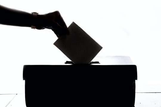 Ruka stavlja glasački papir u kutiju